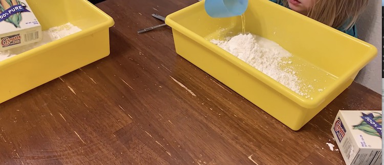 Zoey is still emptying her box of cornstarch into her sensory bin while Ada already did and is now pouring her cup of water into her bin.