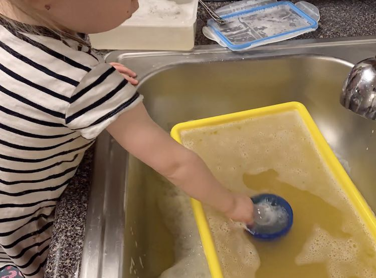 Zoey playing with soapy water in the sink.
