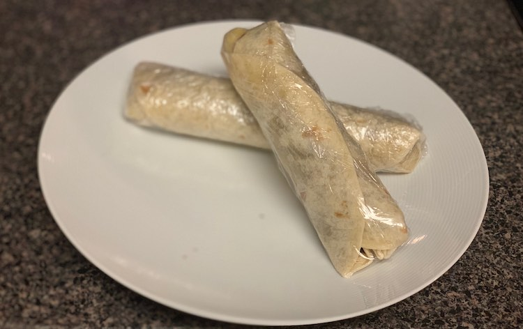 Two made banana wraps individually wrapped with plastic wrap.