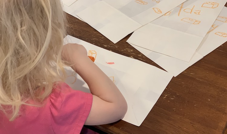 Zoey coloring the favor bags.