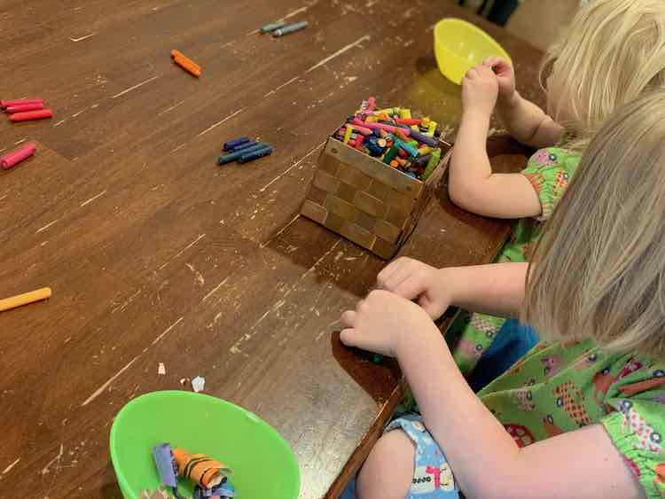 Both kids at the table with a container of crayons between them and each has a bowl for the paper scraps. They've separated the peeled crayons based on their hue.
