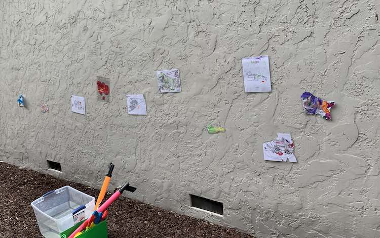 All the targets attached to the wall with the water guns contained in an old DUPLO® box and a bin of water beside it.