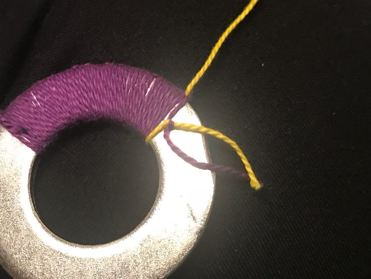 Washer with purple embroidery floss knotted on it and a single strand of yellow knotted. The purple/yellow knot is showing on the last loop around and the loose ends dangle over the naked washer.