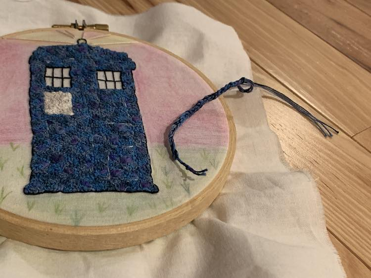 Crocheted string matching the TARDIS' main colors tied off on either end.