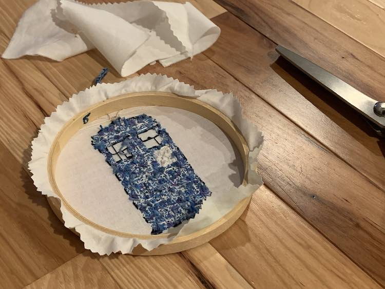 Flipped over embroidery hoop showing the TARDIS butt and the trimmed fabric sticking out the sides.