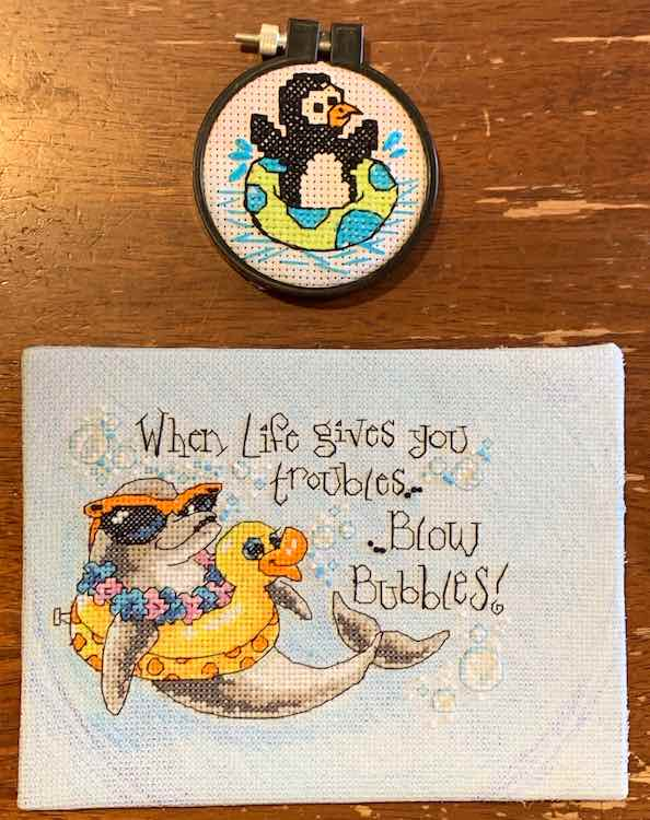 "The two finished and mounted embroidery kits. The smaller circled one (penguin floating in an inner tub) above the dolphin in an inner tube with quote: ""When Life give you troubles... ... Blow bubbles!"""