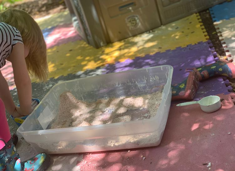 Ada flattening the pail of oobleck sand before dumping it into the bin sitting next to her.