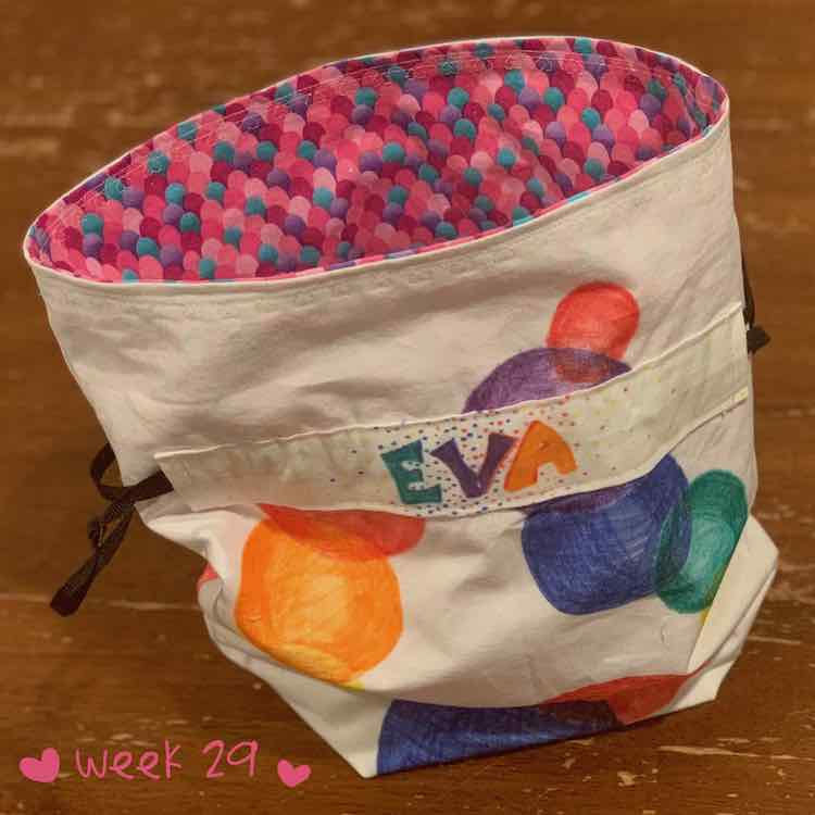 Flat bottom drawstring bag. The inside is made from sparkly scale fabric. The outside is white with colored spheres drawn on. The drawstring is kept in place with some fabric showing the recipient's name.