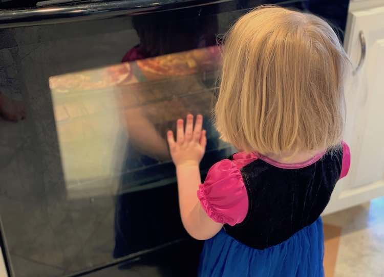 Ada on her knees in front of the lit up oven entranced at the contents inside.