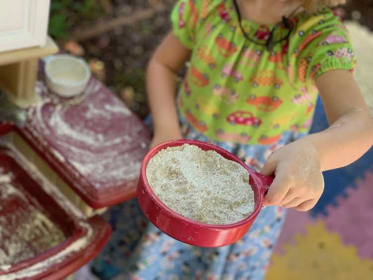 Frying pan of oobleck sand and real sand mixed together. Rest of the image blurred.
