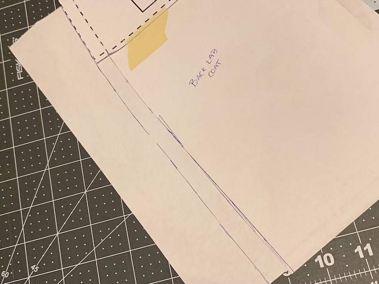 The bottom left corner of the pattern piece is showing. It's taped to a large piece of paper. The bottom is flat and the left side has the new pattern piece edge drawn in.