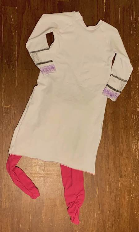 Back of the Doc McStuffins outfit. You can only see the coloring on the sleeves. Pink pants are sticking out below the coat.