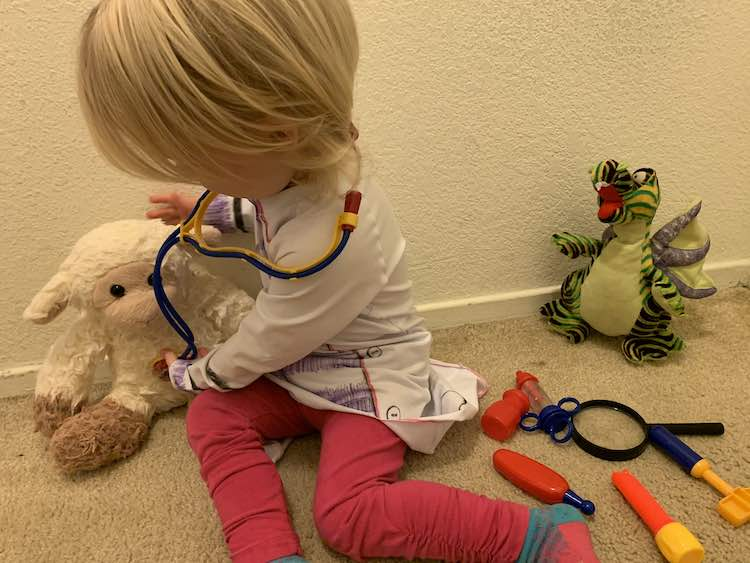 Quick photo before leaving. Zoey siting on the ground with the dragon stuffy and her tools beside her. She's leaning over the lamb toy on the other side of her while checking it's heart rate with her stethoscope.