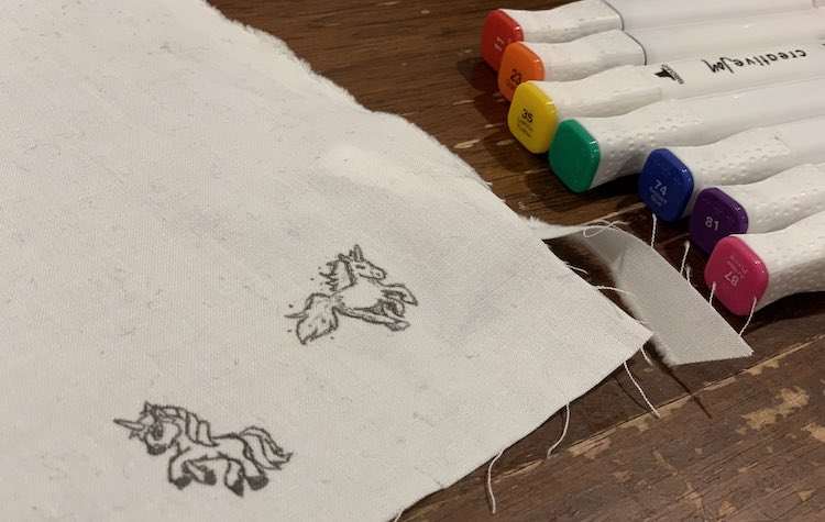 Corner of white woven fabric showing two white unicorns outlined and detailed with a fine-tipped black fabric marker. An array of rainbow colored fabric markers are lined up next to it ready to go.