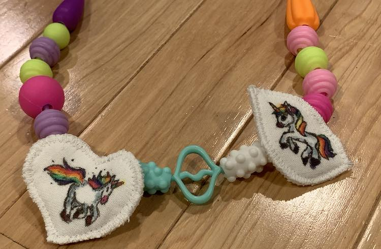 Both pendants attached to snap beads to make a necklace. The pendants are separated by three beads with beads trailing from the pendants into the background edge.