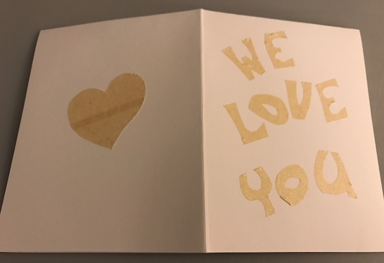 """Card is opened and inside down so you can see the back (left side) and front (right side) of the card. The back has a heart and the front says """"we love you"""" both in masking tape stuck to the paper."""
