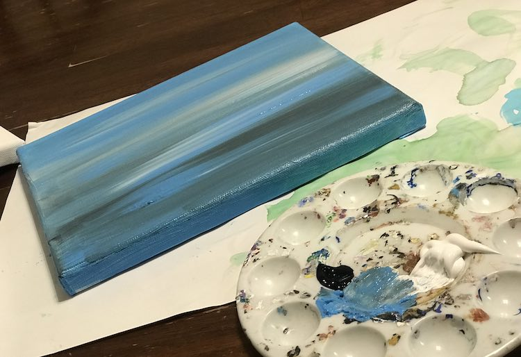 Foreground shows some of a paint palette showing a smudge of blue paint where it used to sit. The black dab and white dollop next to it is only partially used. The finished horizontally streaked blue, white, and black canvas is drying behind the palette.