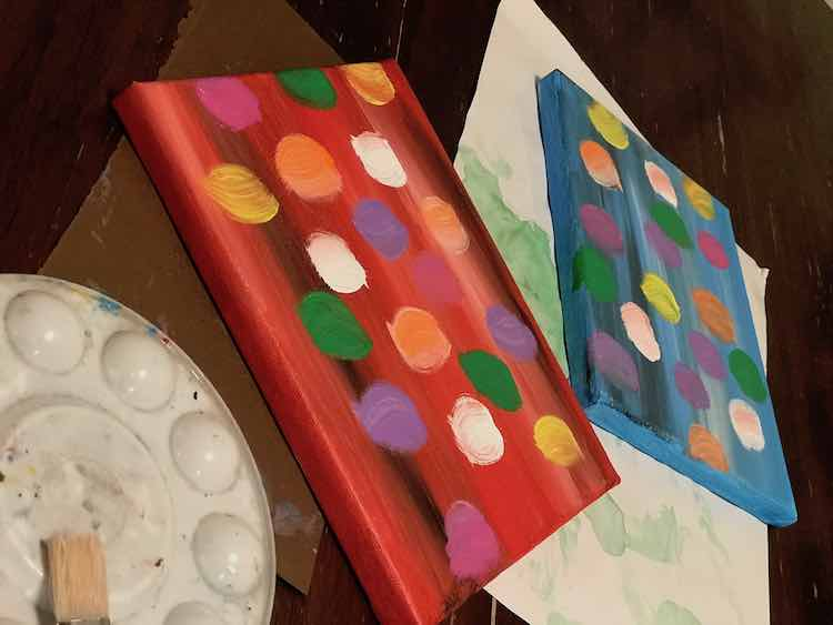 Both canvases with the background and balloons painted on. The cleaned off paint palette and paintbrush are off to the left.