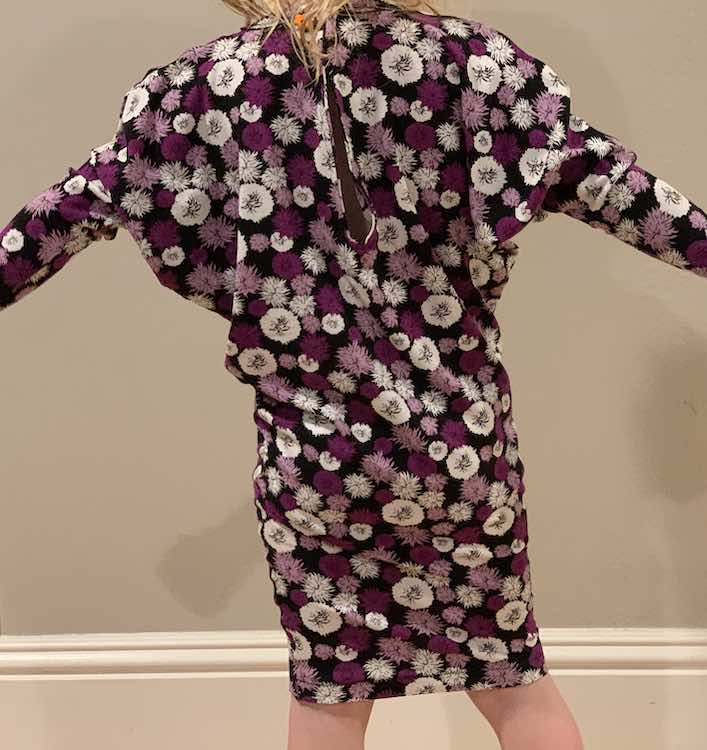 View of the back of Zoey's with her arms raised to the sides. The entire height of the dress is shown but the end of the arms are outside of the photo.