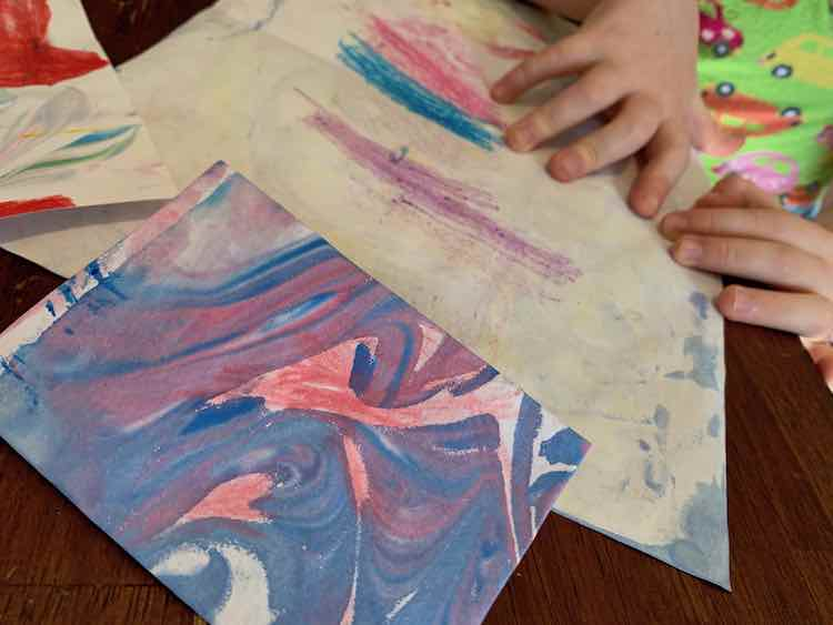 A folded purple and blue card sits at the foreground with red pencil crayon scribbled overtop. The background shows Ada's hands and a slightly marbled paper showing purple, blue, and red pencil crayon marks.