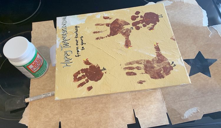 The Thanksgiving turkey handprint canvas is shown below the camera. The glasses are hidden below the canvas and the cardboard is sticking out from underneath. The bottle of mod podge and the foam brush are to the left of the canvas.