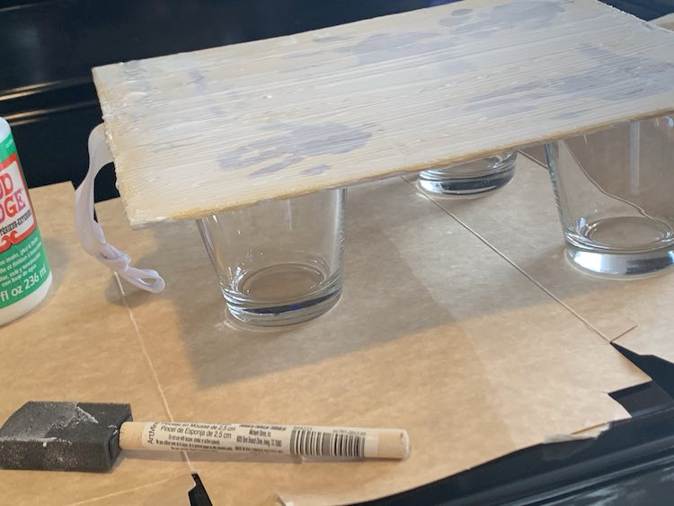 Side view of the canvas allows you to see the drinking glasses holding the canvas up. There are two glasses at either of the bottom corners and one centered at the top. The ribbon at the top of the canvas dangles down and brushes the cardboard. The used foam brush and closed mod podge bottle are visible at the bottom side.