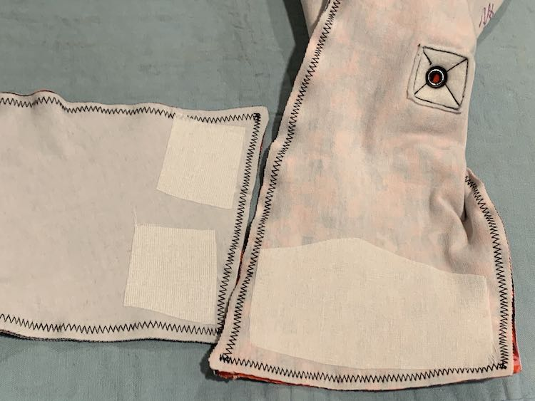 Image shows the interfaced flaps of both kids. On the left is the horizontal laying flap showing two smaller squares of interfacing. The right side shows a vertical laying flap with a large rectangular-ish piece of interfacing. You can also see the underside of the grommet near the top of the image.