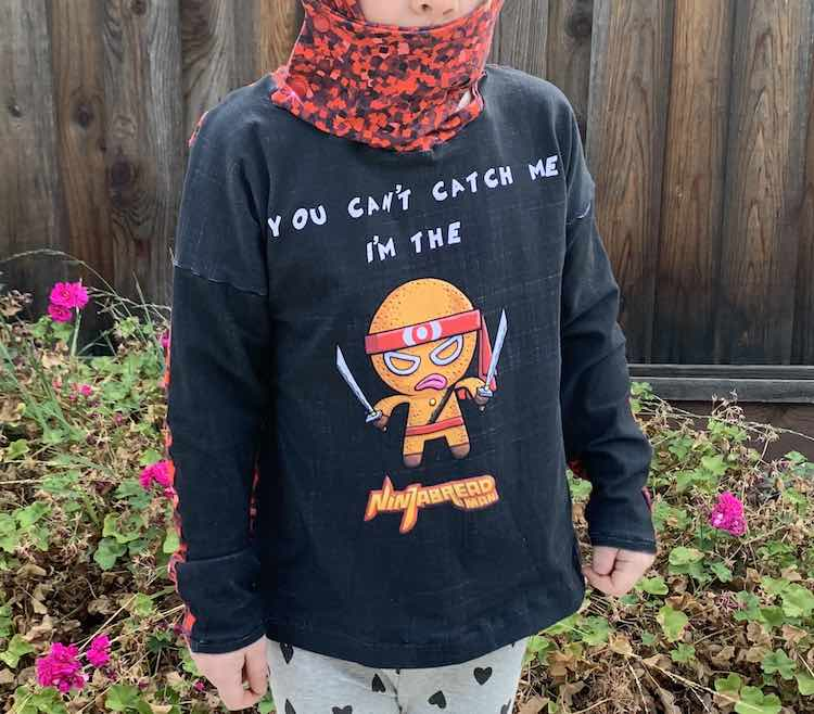 Closeup of Ada's Ninjabread Man top. At the top of the photo you can see the hood flap snapped to the main hood keeping Ada's mouth easily covered.
