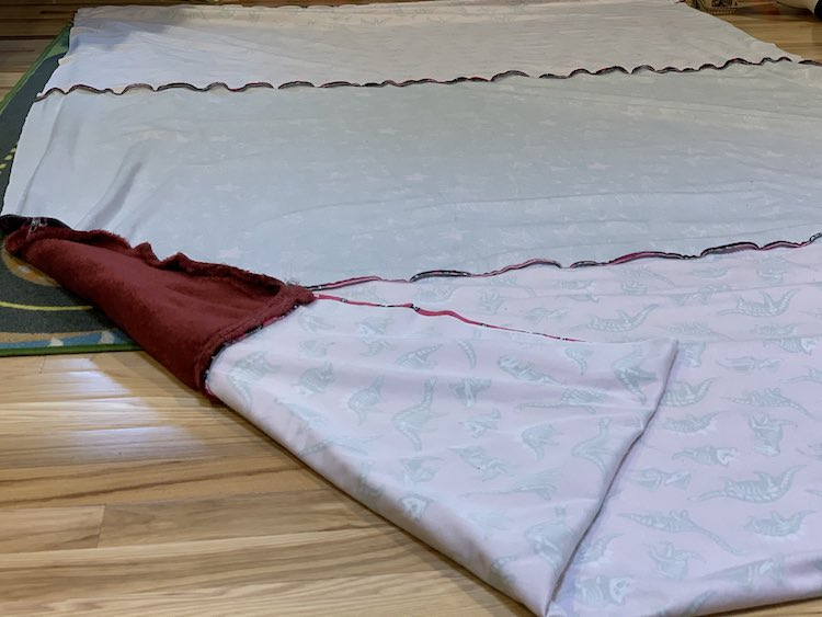 The long blanket has been folded in half, right sides together, so the new center was found and the wrong side is facing up. The folded dinosaur fabric is at the bottom of the picture where the left corner is folded over to show the reverse side and the join between the dinosaur and throw.