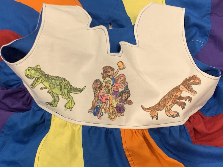 Closeup of the front of the bodice showing the group of LEGO® Friends surrounded by two, looking away, Tyrannosaurus Rex dinosaurs. Surrounding the bodice are the skirt's swirls going away from the bodice and the visible blue liner from the inside of the bodice.
