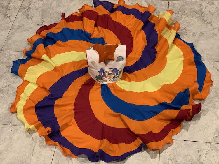 Zoey's dress laid out on the floor. The front of the bodice is shown, along with the back of the lining, as the bodice has been set upright. Around the bodice the skirt is spread out into a fluttery circle.