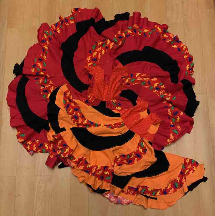 The two dresses laid out on the floor with the photo take above looking down. The larger, red, dress has it's skirt completely open so it's a circle with the bodice in the center. The smaller, orange, dress is laid out at an angle at the bottom.