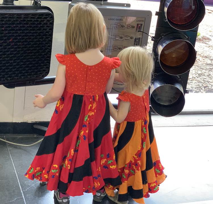 Image shows the back of both kids playing with traffic signals at the local discovery museum.
