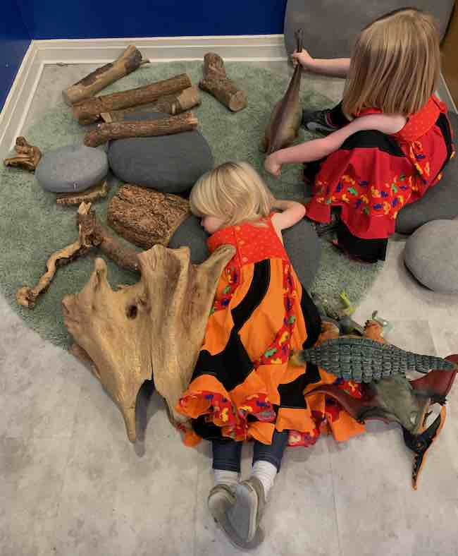 Zoey lays on her tummy on the green grass carpet surrounded by toy dinosaurs and driftwood. Her upper body rests on a 'stone' pillow. Ada sits on her own 'stone' pillow next to her while playing with the brontosaurus.