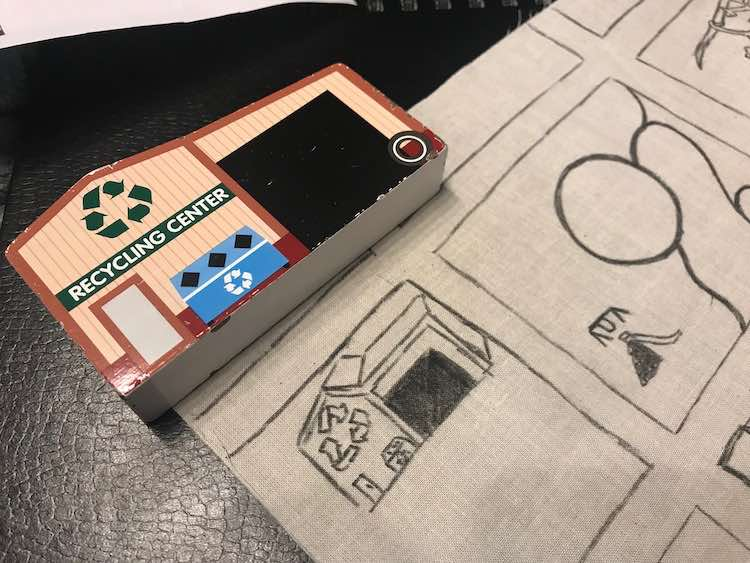 Closeup of the upper left side of the fabric showing a simplified recycling center sketched out. Above it is the 2D wooden Melissa and Doug recycling center toy that I used as a model to sketch it out.