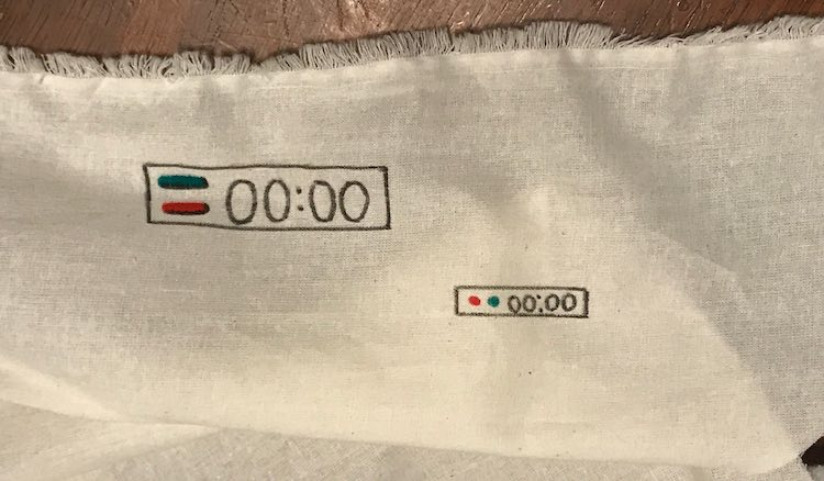 Closeup of the white fabric shows the edge, top of image, and two timers. The upper left timer is larger with two rectangular buttons stacked on top of each other to equal the height of the zeros. The smaller timer is on the lower right and has two round buttons side by side about half the width of the zeros.