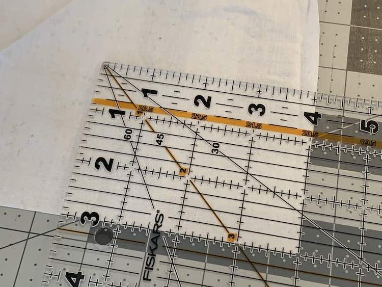 Closeup of the corner of the transparent quilting ruler showing the three by four inch rectangle that I was about to cut out from the fabric.