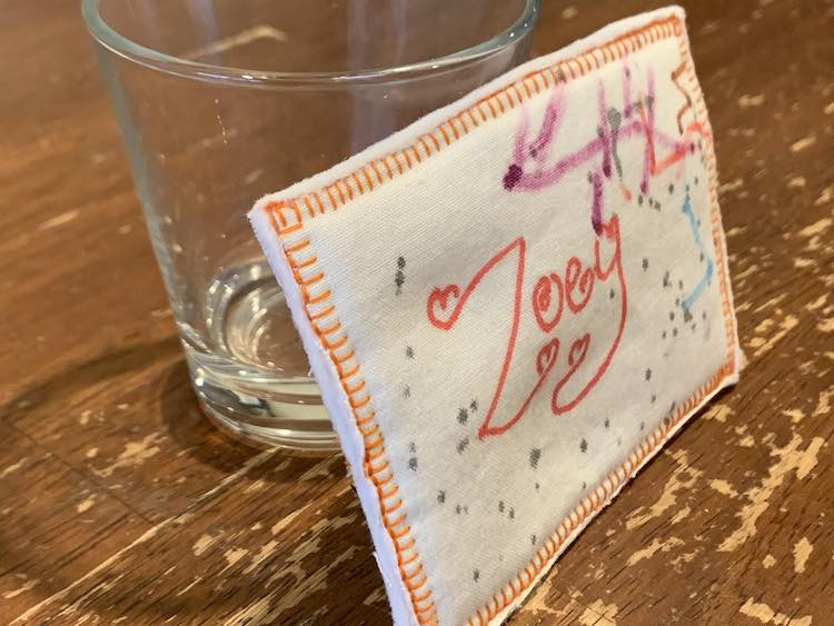 Closeup of Zoey's name tag leaned against a transparent empty glass.