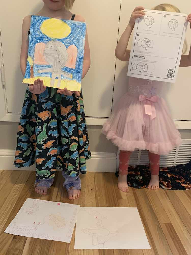 Ada and Zoey standing beside each other. At their feet are two of Ada's doodles on the ground. Ada, on the left, holds her version of Gerald while Zoey, on the right, holds the instruction sheet for Gerald the Elephant.