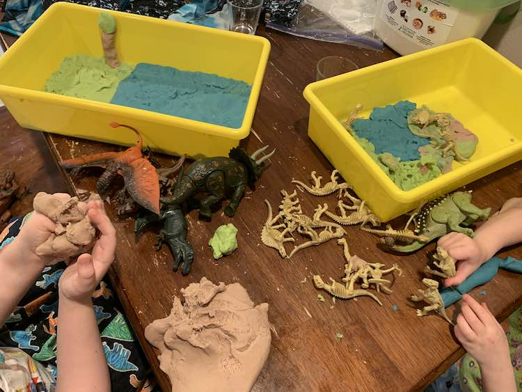 Image shows both girls sitting near each other working on creating a scene in their yellow sensory bins using blue, green, and brown playdough. The dinosaurs are scattered over the table between them and the playdough.