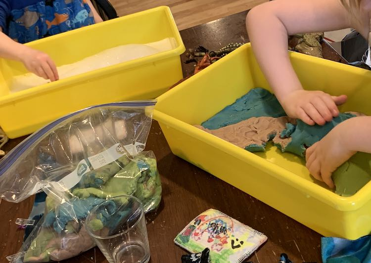 Image shows two bins on the table with a bag of blue, green, and brown playdough between them. The bin furthest away is partially filled with bubbles while Zoey is holding something in it. The bin closest to the camera shows Ada pealing up the layers of playdough from her sensory bin.