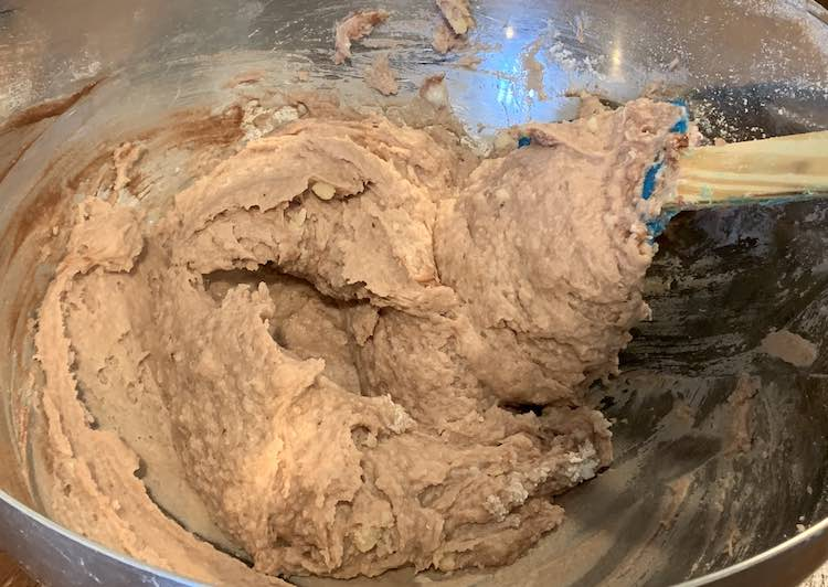 View of a metal bowl with brown sludge in it. You can see a mostly covered blue spatula in the bowl, used for mixing, and streaks of dark brown, unmixed, paint along the side.