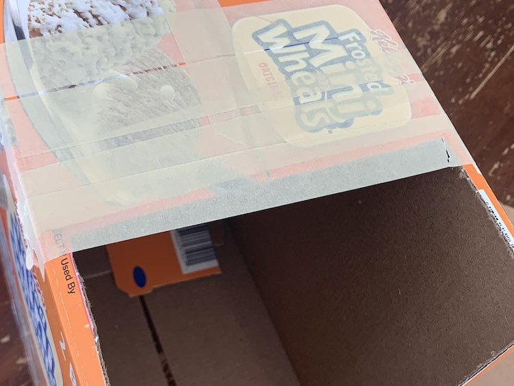 View of the top of the box showing the last piece of tape stretching across the width of the box overlapping with the cut edge. The right side has a rip in the tape leading to that corner.