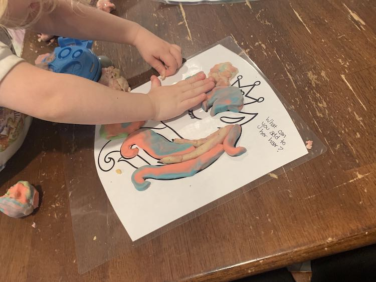 """Image shows a laminated unicorn coloring page with the text """"What can you add to her hair?"""". The hair is partially filled in with pastel playdough and Zoey leans over the page pushing some more into it."""