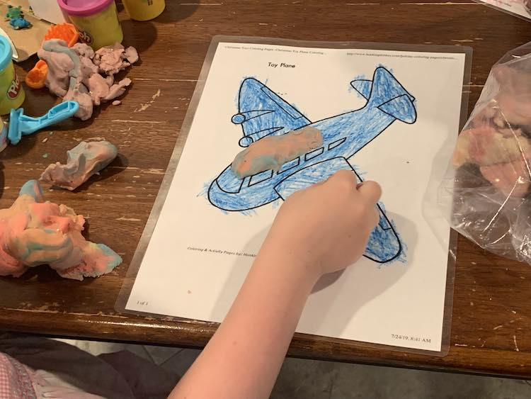 Image shows a blue colored airplane with some pink mottled playdough forming part of it's roof.