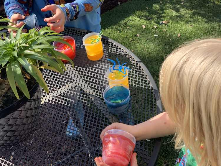 Closeup of part of an outdoor table with the six colored cups lined up. Zoey is closer to the camera holding the red ice cup while Ada is furthest away getting the blue ice out of the cup.