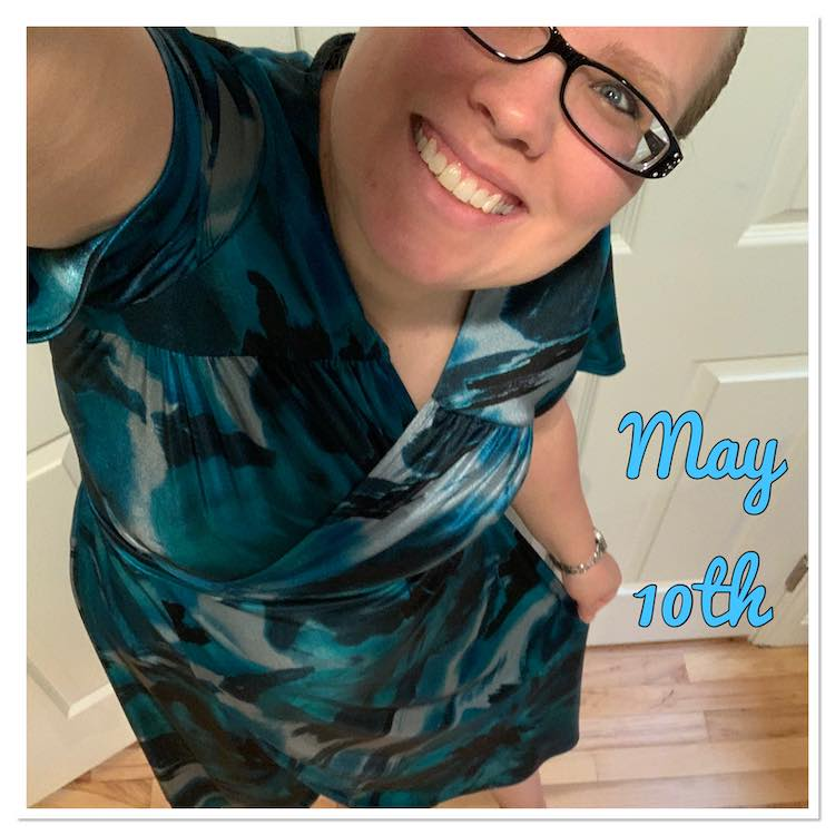 Selfie view showing one eye and the bottom of my face, tilted to fit, along with my dress. It's a wrap dress with slink ITY in blues, grey, and black. To the right of me are the words, in blue, saying 'May 10th'.