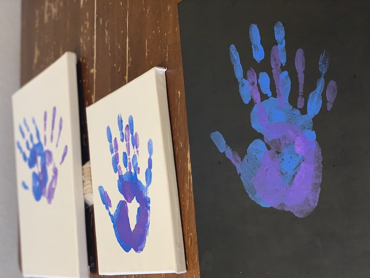 View of the the three paintings side by side on the table. The rightmost one has a black background and the blue and purple handprints are stacked over one another. The center small canvas is white with the prints, again, stacked. The far left and slightly blurry (in the image) is also white but just as large as the right canvas. Here the two handprints are slightly overlapping with the top of the hands leaning away from each other.