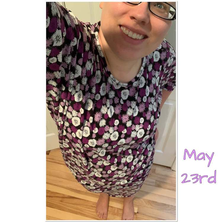 Selfie view, back to one eye, of a purple and white flowered dress. The neck is a crew neck with a binding and the sleeves end at the elbows. The dress reaches to my knees but it's hard to see the length from this angle. The shirt has a large batwing so you can see extra fabric draping at the armpit of the arm holding the phone.