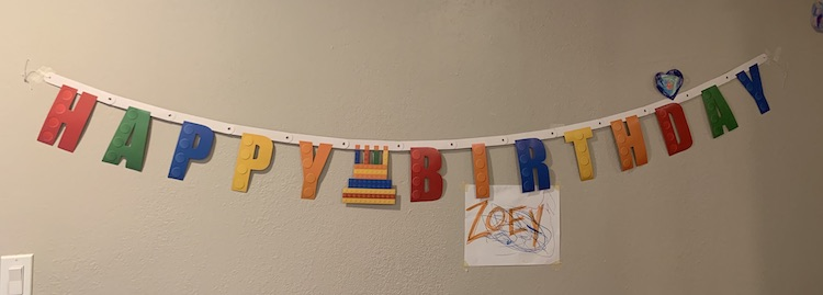 Closeup of the LEGO® Happy Birthday banner on the wall. There's masking tape on either end keeping it up. Over the d in Birthday one of Ada's older hearts hang. Under the IR in Birthday there's a doodled white sheet of paper with the word ZOEY in orange capital letters.